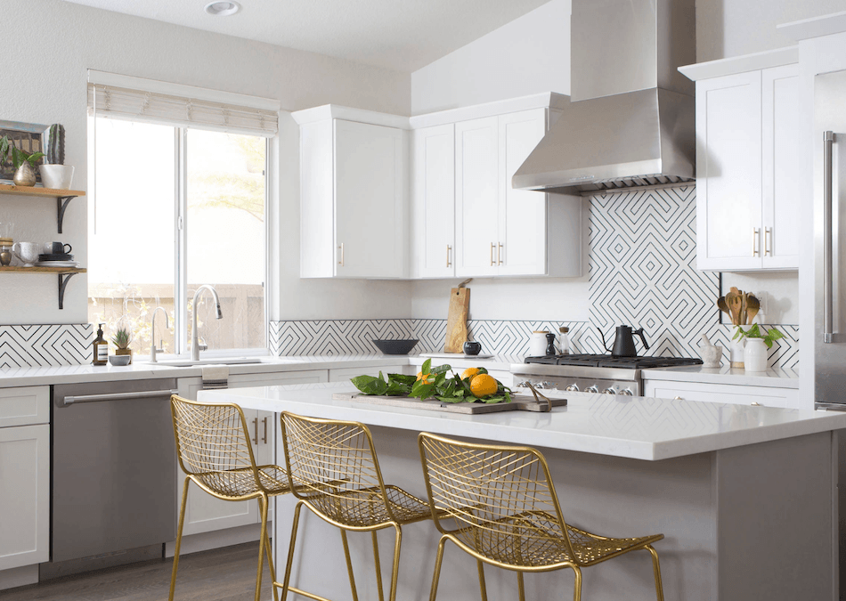modern kitchen with geometric tiles and brass chairs