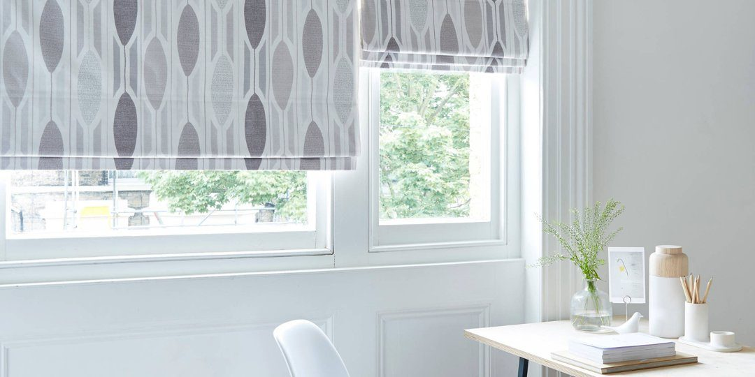 pattern blockout roller blinds in room with desk